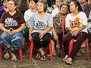 03 AUGUST 2016 - BANGKOK, THAILAND: Residents of the Pom Mahakan slum listen to Bangkok Metropolitan Administration (BMA) listen to BMA officials during a community meeting in the Pom Mahakan slum. BMA officials told the residents of the slum that they must leave the fort and that their community will be torn down. The community is known for fireworks, fighting cocks and bird cages. Mahakan Fort was built in 1783 during the reign of Siamese King Rama I. It was one of 14 fortresses designed to protect Bangkok from foreign invaders. Only of two are remaining, the others have been torn down. A community developed in the fort when people started building houses and moving into it during the reign of King Rama V (1868-1910). The land was expropriated by Bangkok city government in 1992, but the people living in the fort refused to move. In 2004 courts ruled against the residents and said the city could take the land. Eviction notices have been posted in the community and people given until April 30 to leave, but most residents have refused to move. Residents think Bangkok city officials will start evictions around August 15, but there has not been any official word from the city.      PHOTO BY JACK KURTZ