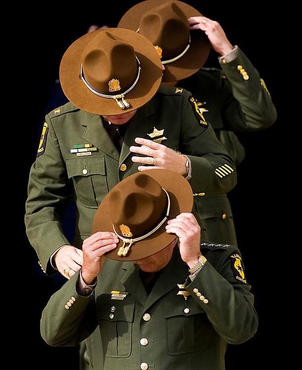Herald &amp; Review/Stephen Haas<br /> Illinois State Police officers put on their hats as they file out of St. Patrick's Church in Pana, Ill., Wednesday, Oct. 31, 2007, after the funeral mass for Brian McMillen. McMillen, an officer with the State Police, was killed by a drunk driver in a crash early Sunday morning.