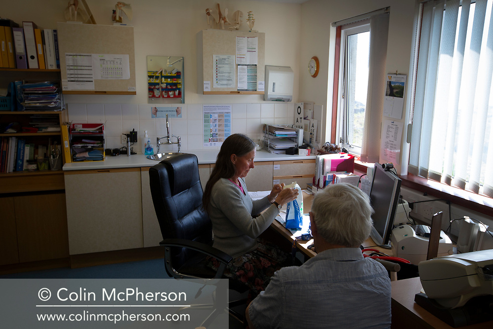 GP Dr Jan Brooks during a patient consultation with John Bridges at  the medical practice on the the Inner Hebridean island of Colonsay on Scotland's west coast.  The island is in the council area of Argyll and Bute and has an area of 4,074 hectares (15.7 sq mi). Aligned on a south-west to north-east axis, it measures 8 miles (13 km) in length and reaches 3 miles (4.8 km) at its widest point, in 2019 it had a permanent population of 136 adults and children.