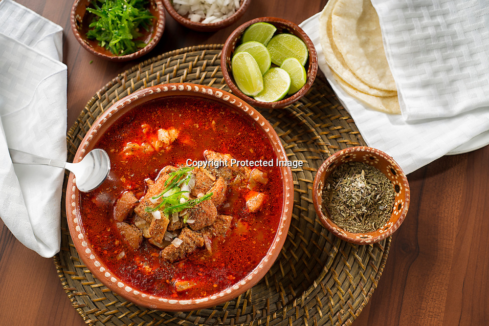 Menudo bowl with all the fixings you need, chopped onion, lime, oregano, sliced chili pepper.
