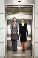 Businesswomen Side by Side in Elevator portrait front view