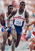 BARCELONA, SPAIN - AUGUST 8:  Carl Lewis of the USA runs the anchor leg of the Men's 4 x 100 meter relay event of the Athletics competition of the XXV Olympiad on August 7, 1992 at the Montjuic Olympic Stadium in Barcelona, Spain.  The USA team set a new world record of 37.40 in the race.  Visible at left after handing off to Lewis is Dennis Mitchell of the USA. (Photograph by David Madison/Getty Images)
