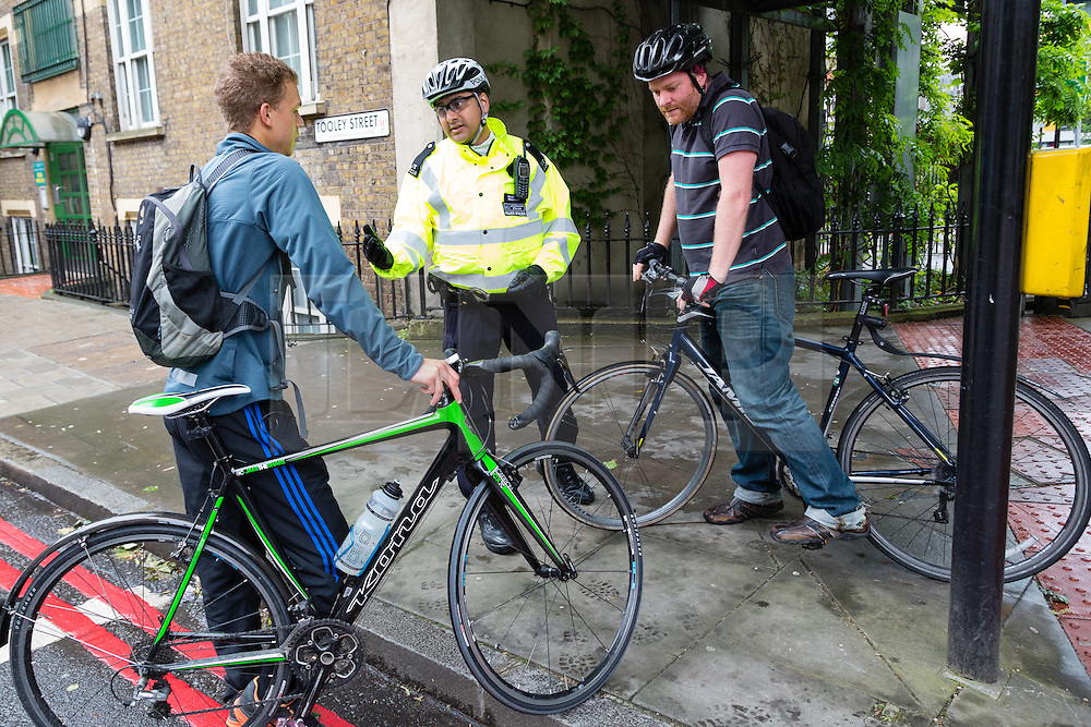 © Licensed to London News Pictures. 27/05/2014. London, UK. A Police officer gives advice to cyclists at an Operation Safeway road safety event held at the junction of Tooley Street and Tower Bridge Road in London on 27th May 2014. A seven week pilot of Operation Safeway was carried out late last year in response to a series of tragic cyclist and pedestrian deaths on London's roads, where Police officers were deployed at key junctions across the capital, enforcing road safety and giving advice to road users during rush hours. Operation Safeway will now continue at key junctions across London to build awareness and promote safety for all road users. Photo credit : Vickie Flores/LNP