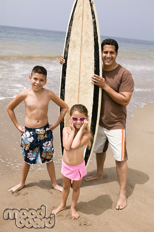 Portrait of man holding surfboard with children on beach