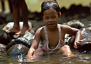 A young child washing in a river in the Philippines