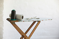 Spools of thread and scissors on ironing board indoors