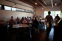 A waiter walks through the crowded dining room at The Block Restaurant in Webster Groves, St. Louis, MO.