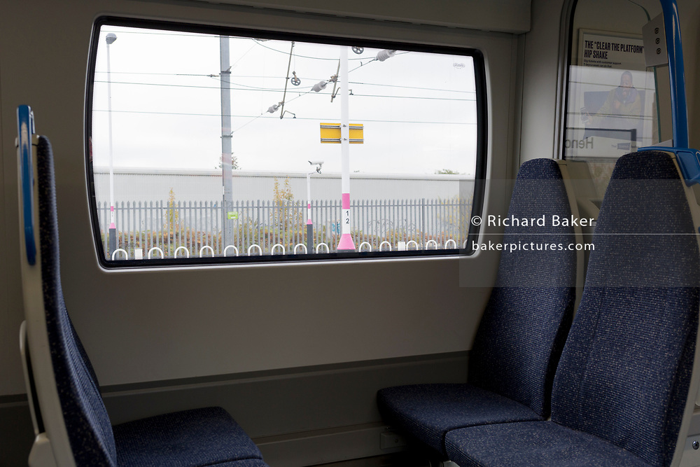 A generic landscape outside of a station platform sign a CCTV camera, see through the window seat of a north-bound Thameslink train, on 15th October 2019, in London, England.