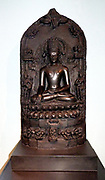 Crowned Buddha. AD1000-1100 Pala dynasty. Bihar, North-East India, Basalt.  This image shows Buddha Shakyamuni at the moment of his enlightenment at Bodhgaya.  He wears the crown and ornaments of a king with the simple monastic robes of a monk, together evoking his spiritual authority.