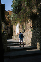 """PISCIOTTA, ITALY - 22 APRIL 2018: A man walks in the narrow streets of the historical center of Pisciotta, Italy, on April 22nd 2018.<br /> <br /> Former restaurant owners Donatella Marino and her husband Vittorio Rimbaldo have spent the recent years preparing and selling salted anchovies, called alici di menaica, to a growing market thanks to a boost in visibility from the non-profit Slow Food.  The ancient Menaica technique is named after the nets they use brought by the Greeks wherever they settled in the Mediterranean. Their process epitomizes the concept of slow food, and involves a nightly excursion with the special, loose nets that are built to catch only the larger swimmers. The fresh, red anchovies are immediately cleaned and brined seaside, then placed in terracotta pots in between layers of salt, to rest for three months before they're aged to perfection.While modern law requires them to use PVC containers for preserving, the government recently granted them permission to use up to 10 chestnut wood barrels for salting in the traditional manner. The barrels are """"washed"""" in the sea for 2-3 days before they're packed with anchovies and sea salt and set aside to cure for 90 days. The alici are then sold in round terracotta containers, evoking the traditional vessels that families once used to preserve their personal supply.<br /> <br /> Unlike conventional nets with holes of about one centimeter, the menaica, with holes of about one and half centimeters, lets smaller anchovies easily swim through. The point may be to concentrate on bigger specimens, but the net also prevents overfishing."""