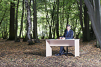 Business man sitting at desk in middle of forest working