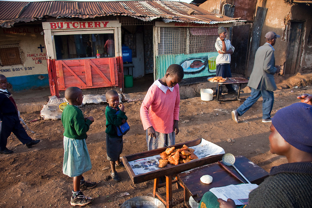 A girl buys a pastry made from fried dough from a vendor in the Kibera slum, Nairobi Kenya. Kibera is Africa's biggest slum with nearly one million inhabitants., most of whom have limited access to clean water and sanitation.