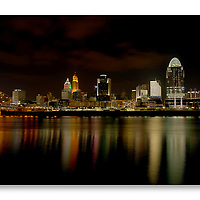Cincinnati skyline at night with city lights reflected in the Ohio River and illuminating the clouds in the sky.