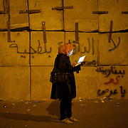 December 11, 2012 - Cairo, Egypt: An female protestor stands outside the presidential place in Cairo, where tens of thousands gathered to voice their anger at the planned constitution, which will be put to a referendum next Saturday...The Egyptian army has reportedly called talks between President Mohamed Morsi and the opposition to end violent protests against a draft constitution...Sporadic clashes between supporters and opponents of president Mohamed Morsi, erupted in the past week over his assumption of extraordinary powers and the scheduling of the referendum. (Paulo Nunes dos Santos/Polaris)