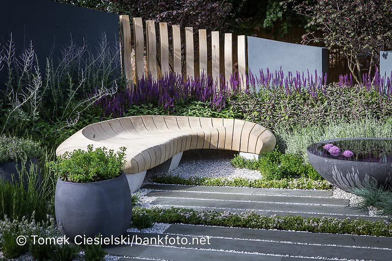 Sculptured bench, striped paving interspersed with herb stripes, and pots of herbs