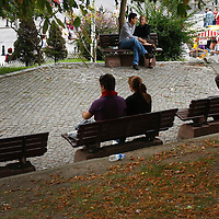 People relax on benches in Mehmet Akif Ersoy Park in Istanbul, Turkey