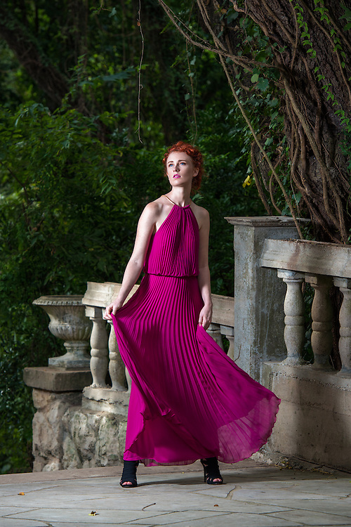 Young woman posing in hot pink dress surrounded by beautiful grounds.