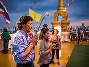 20 NOVEMBER 2015 - BANGKOK, THAILAND: People pray at the top of Wat Saket during the annual temple fair. Wat Saket is on a man-made hill in the historic section of Bangkok. The temple has golden spire that is 260 feet high which was the highest point in Bangkok for more than 100 years. The temple construction began in the 1800s in the reign of King Rama III and was completed in the reign of King Rama IV. The annual temple fair is held on the 12th lunar month, for nine days around the November full moon. During the fair a red cloth (reminiscent of a monk's robe) is placed around the Golden Mount while the temple grounds hosts Thai traditional theatre, food stalls and traditional shows.     PHOTO BY JACK KURTZ