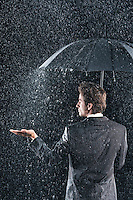Businessman sticking hand out from under umbrella to feel rain back view