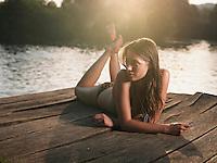 Young woman in bikini lying on jetty looking away
