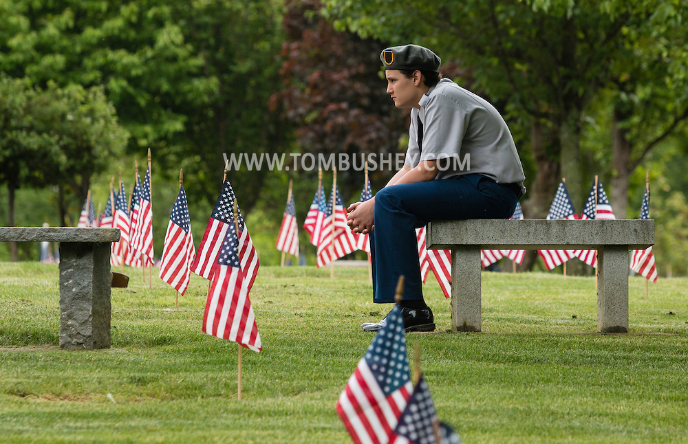 Goshen, New York - A Minisink Valley High Schol Army JROTC cadets sits on a bench after placing American flags by a veterans' graves at the Orange County Veteran's Cemetery in preparation for Memorial Day on May 24, 2016.