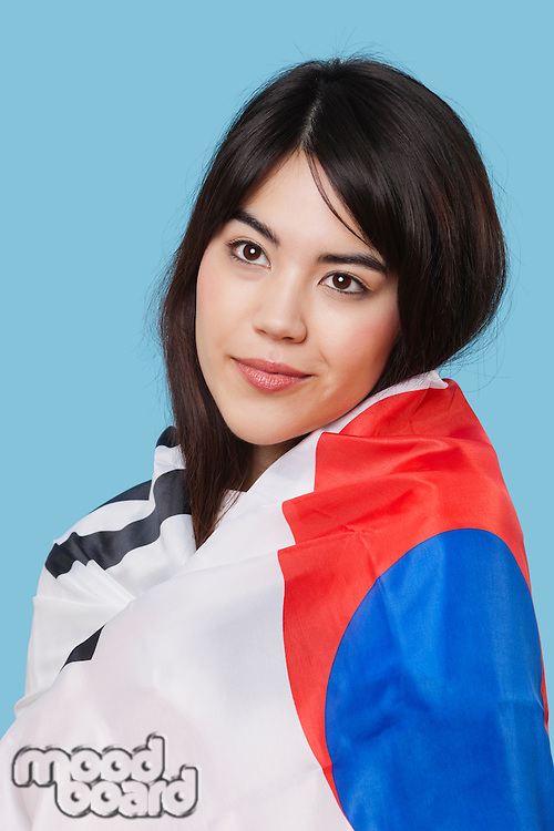 Patriotic young woman wrapped in Korean flag over blue background