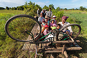 "A family travel on the ""Bamboo Train' in Battambang, Cambodia. The railway is no longer used by passenger trains but local people have built bamboo platforms which rest upon old train wheels, allowing them to still travel on the rails."
