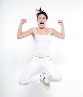 beautiful young woman exercising jumping happy screaming on studio isolated white background