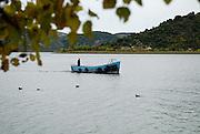 Monk in blue boat on water, Krka Franciscan Monastery, island of Visovac, Krka National Park, Croatia