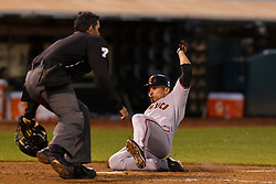 June 18, 2011; Oakland, CA, USA;  San Francisco Giants center fielder Andres Torres (56) slides into home in front of MLB umpire Manny Gonzalez (79) to score a run against the Oakland Athletics during the fifth inning at the O.co Coliseum.