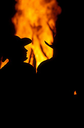 Silhouette of cowboys standing beside a bonfire at night