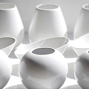 monochromatic view of contemporary white vases and bowls, sunlit