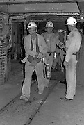 """Banksman, Alan Gilburn, collecting checks from Eric Holmes as miners come up from underground at Markham Main Armthorpe Colliery. Miner in front is """"Smokie"""" Joe Taylor at rear in cage is Joe """"Killer""""Smith. National Coal Board, Doncaster Area 21/06/1983."""