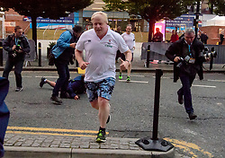 © Licensed to London News Pictures. 02/10/2017. Manchester, UK. A police close protection officer falls over while running with Foreign secretary BORIS JOHNSON on the morning of the second day of the Conservative Party Conference. The four day event is expected to focus heavily on Brexit, with the British prime minister hoping to dampen rumours of a leadership challenge. Photo credit: Ben Cawthra/LNP