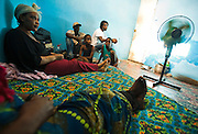 Liberian nationals Fatou Jallah (left) and her sister Nina sit with Nina's children and friends Michael Johnson (back left) and Solo Biee, also Liberians, in the room where Nina lives with her family in Dakar, Senegal on Thursday July 16, 2009. Nina says she's not following the Charles Taylor trial and wishes people could just move on..
