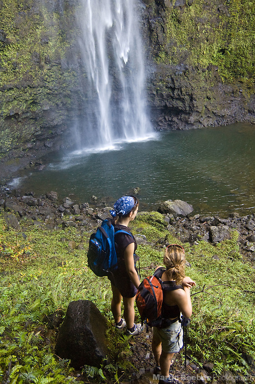 A pair of hikers gaze upon Hanakapiai Falls, Kauai, Hawaii