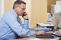 Businessman talking on mobile phone using laptop in office