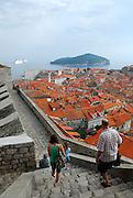 People walking down very steep steps of Minceta Tower, looking over tiled roofs of Dobrovnik old town, Croatia