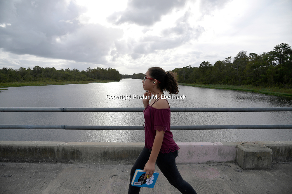 A pedestrian walks along a bridge over the Little Econlockhatchee River in Jay Blanchard Park Saturday, Oct. 21, 2017, in Orlando, Fla. (Photo by Phelan M. Ebenhack)