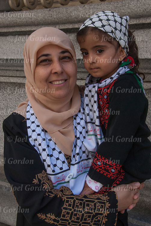 Portrait of American Palestine Muslim  mother holding her 3 year old daughter. <br /> <br /> They are one of the many faces of people showing their ethnic pride who were marching and in the crowds from the 2014 Muslim Day Parade in New York.<br /> <br /> She is wearing the tradition headdress / headdress scarf call a Hijab.
