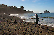 A woman walks along the sandy beach at Van Damme State Beach - Van Damme State Park, California