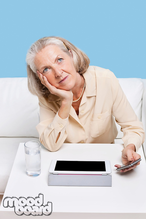 Contemplative woman using cell phone and tablet PC at table