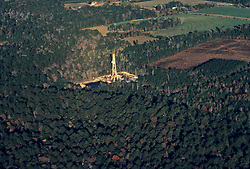 Stock photo of the aerial view of an on-shore rig surrounded by forest
