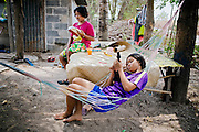While her cousin is reading a school book, Phatsorn Bunmasen, 14, is playing with a toy guitar and relaxing on an hammock in the front yard of her home in a village near Ubon Ratchathani, northeast Thailand.