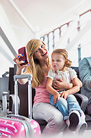 Portrait of young teenage girl taking selfie with her little sister while waiting for boarding in airport
