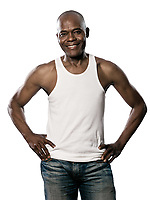 Portrait of a happy african afro American man with hands on hips jeans and sleeveless t-shirt standing in studio on white isolated background
