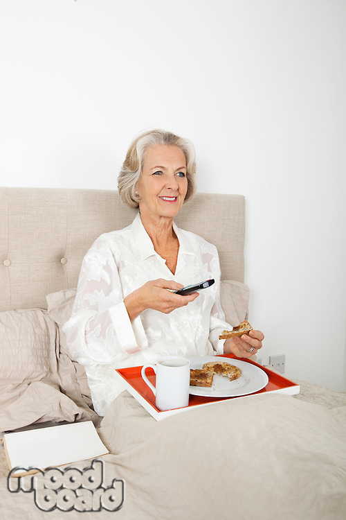 Happy senior woman watching TV while having breakfast in bed