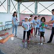 In Ein El-Hilweh refugee camp, home to 75.000 Palestinians. The girls play a race game where two teams compete to fill up a beaker with water. It is summer break in the UNWRA school and Naba'a runs Play and Learn sessions in the empty school for vulnerable children. They aim is to give them a safe space to express themselves with out fear of repression. Developmental Action Without Borders(Naba'a) work in Palestinian refugee camps across Lebanon to help children in the camps.  The camps are densely over-crowded and many of the children are 4th generation refugees living in Lebanon with no citizenship or rights and under immense pressure. Naba'a is a mix of Palestinians and Lebanese and aim to give children a sense of security and freedom to express their needs and rights.Naba'a operates in communities governed by a multitude of political parties and religious groups and Naba'a keeps a strict independed line from any affiliation with any groups.