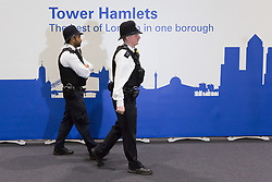 © Licensed to London News Pictures. 04/05/2018. London, UK. Police officers walk in front of a Tower Hamlets sign shortly before the result for the Mayor of Tower Hamlets is announced at the Excel Centre in London. Photo credit: Vickie Flores/LNP