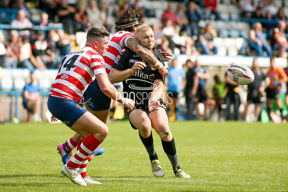 Bradford Bulls loose forward Damian Sironen (10) takes a hit after passing the ball during the Kingstone Press Championship match between Oldham RLFC and Bradford Bulls at Bower Fold, Oldham, United Kingdom on 13 August 2017. Photo by Simon Davies.